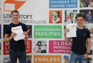 Two students holding up their exam results